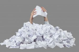 Hands with empty crushed paper reaches out from big heap of crumpled papers