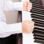 music and instrument concept - close up of child hands in fists hitting the piano