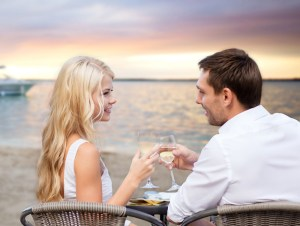 summer holidays, people, romance, travel and dating concept - couple drinking wine in cafe on sunset beach