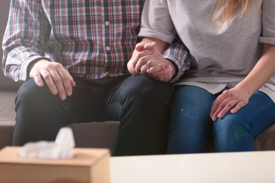 Close-up of a couple holding hands together while sitting on a couch
