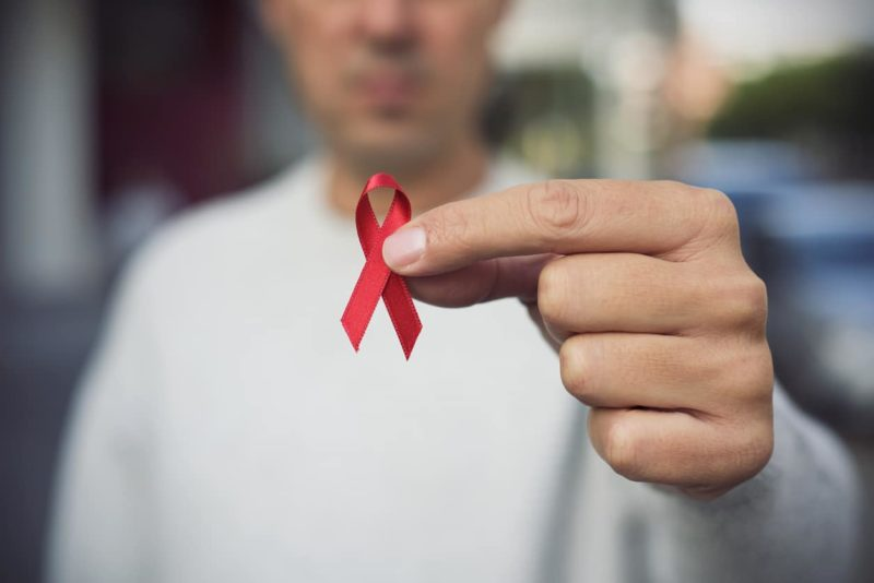 Man holding red hiv aids awareness ribbon