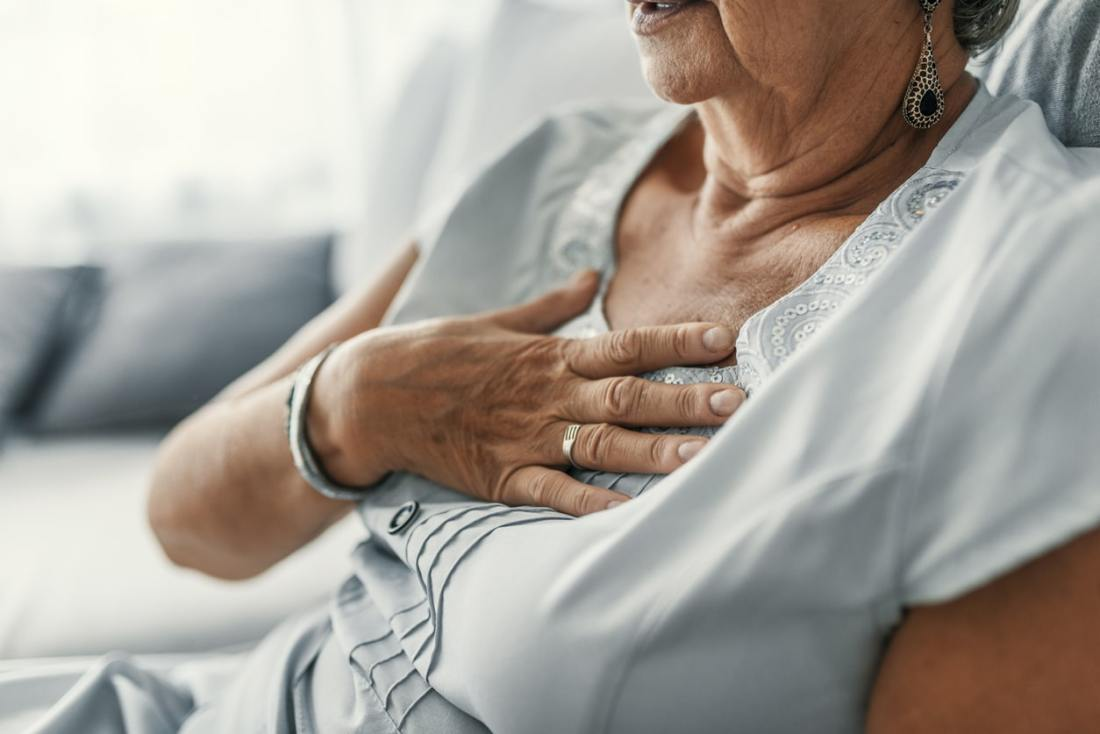 older woman sitting with her right hand on her chest in pain