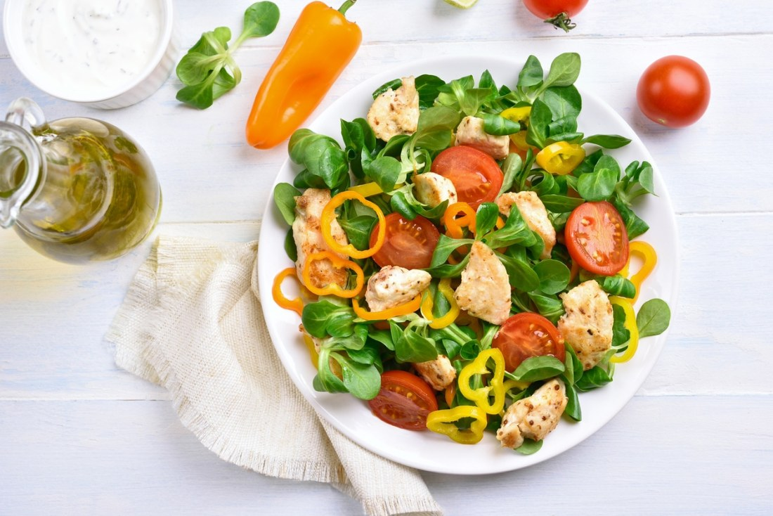 fresh salad with tomatoes and chicken served on a white bowl with a side of dressing