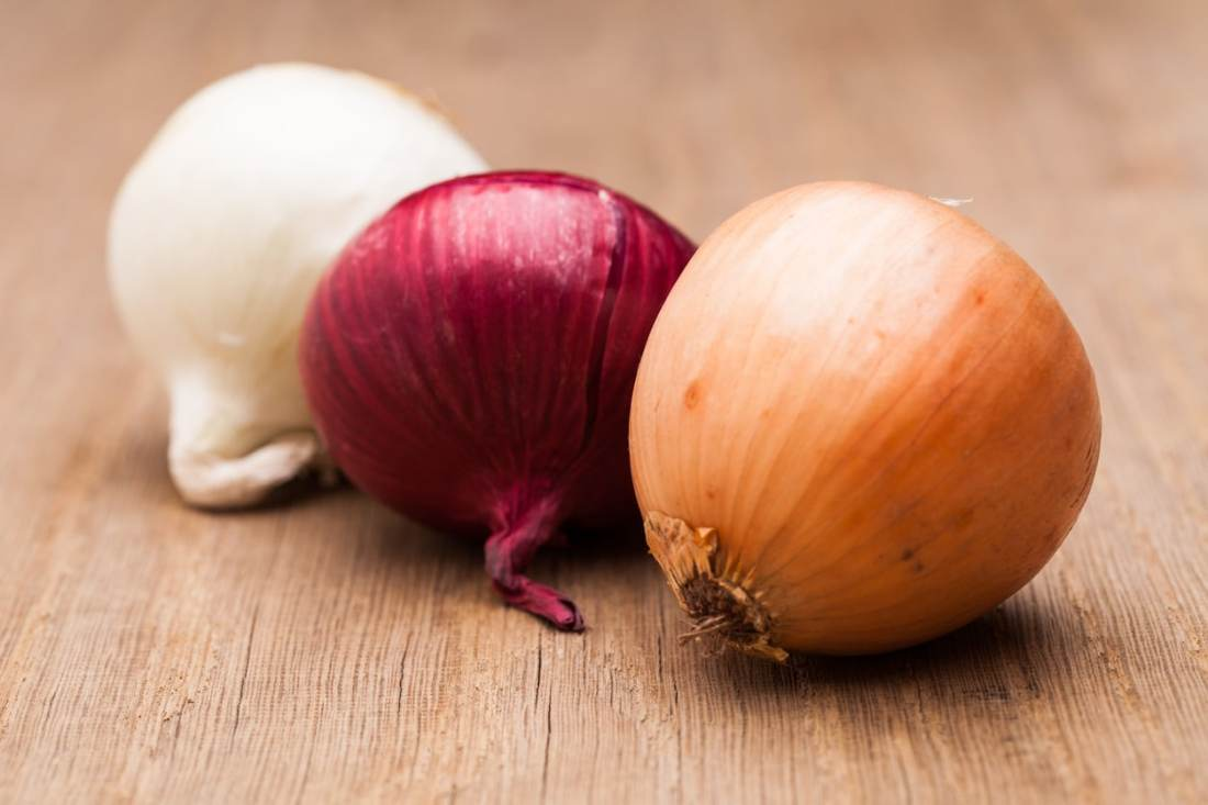 white, red, and yellow onion on wood slab