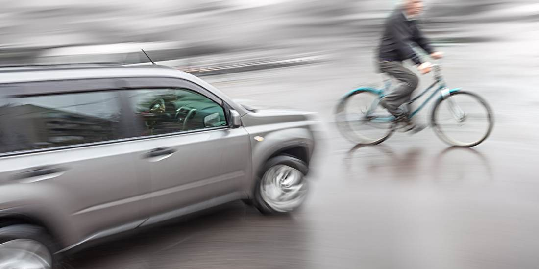 Dangerous city traffic situation with a cyclist and cars in motion blur - Pedego Bike Recall