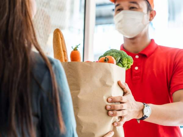 courier delivery person wearing a mask and handing a woman groceries
