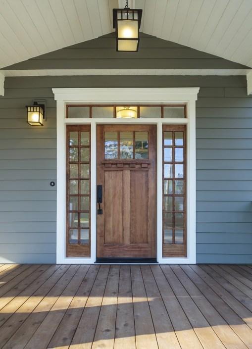 Dark natural wood doorway flanked by windows