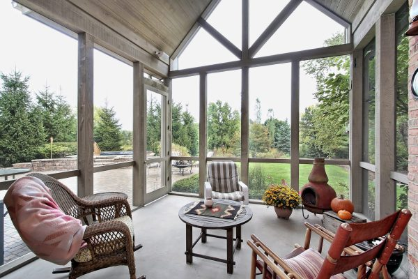 glass enclosed patio with chairs and table