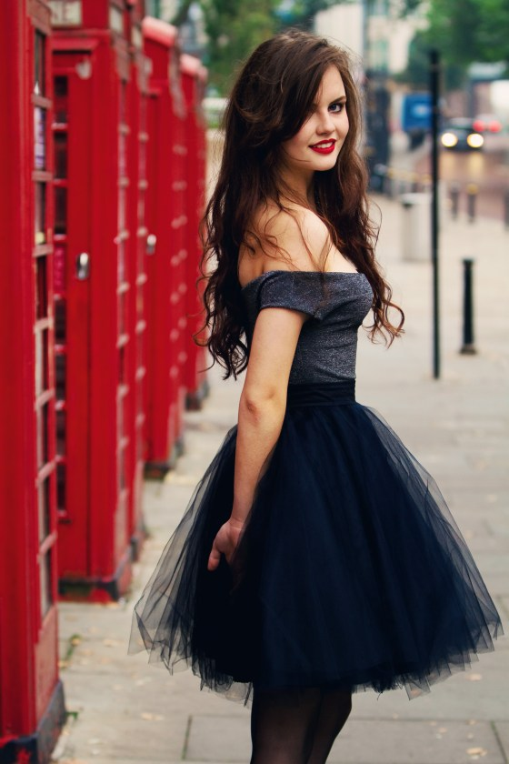 brunette-stood-in-front-of-phone-boxes