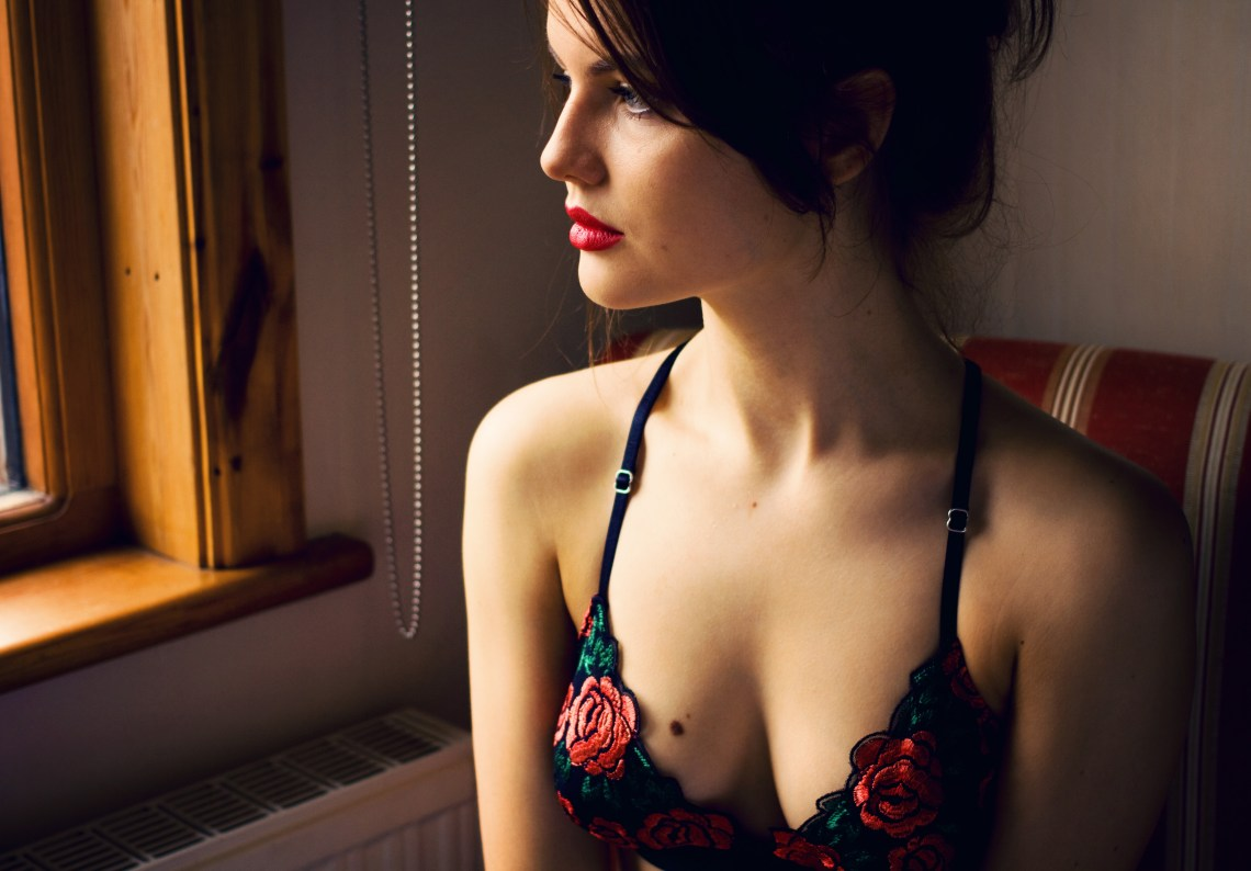 Girl wearing black and red embroidered bra looking out of window