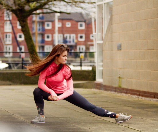 Girl with wind blown hair doing side lunges
