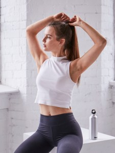 Female fitness model holding arms over head