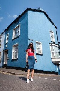 Young woman stood in front of blue painted corner house