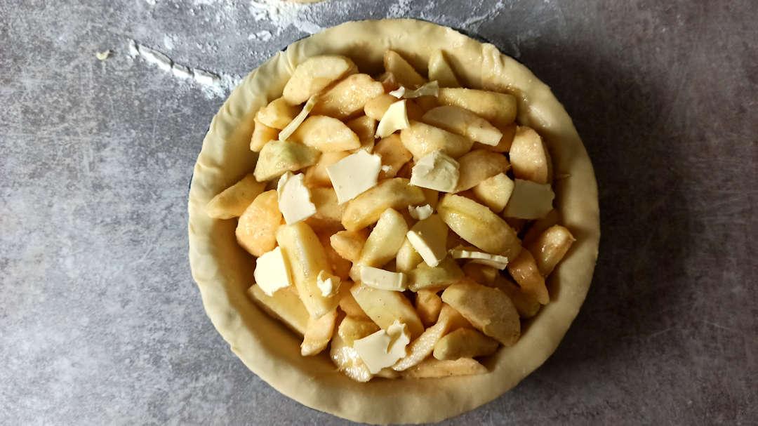 Parsemer de petits morceaux de beurre sur l'apple pie traditionnelle