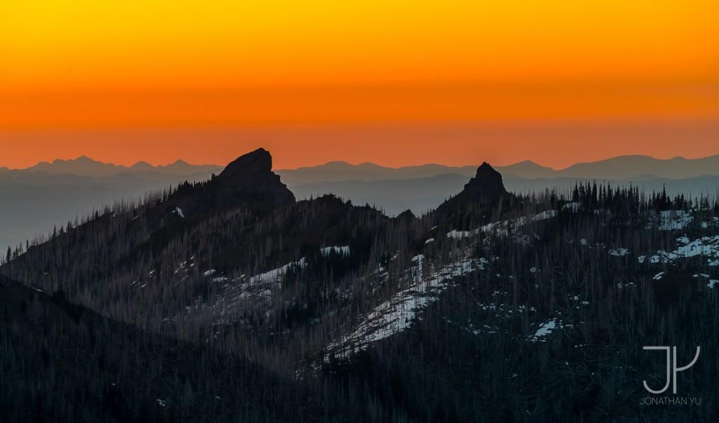 Seemingly endless ridges lie beyond two sharp peaks at sunset