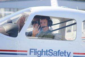 teen camper at cockpit of FlightSafety aircraft taxiing for take off.