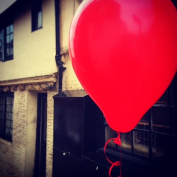 A red balloon floats down an old side street