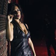 Brunette model dressed in black leather leans against wall in an alleyway