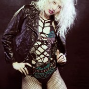 Fashion portrait of blonde model in leather jacket and fishnet pantyhose.
