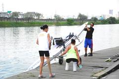 César ajuda as meninas com o barco para começar o treino de remo (foto: Denise Eloy)