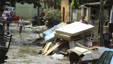 Moradores da Vila São José caminham entre o que sobrou de seus móveis após enchente:consequência final da falta de planejamento administrativo