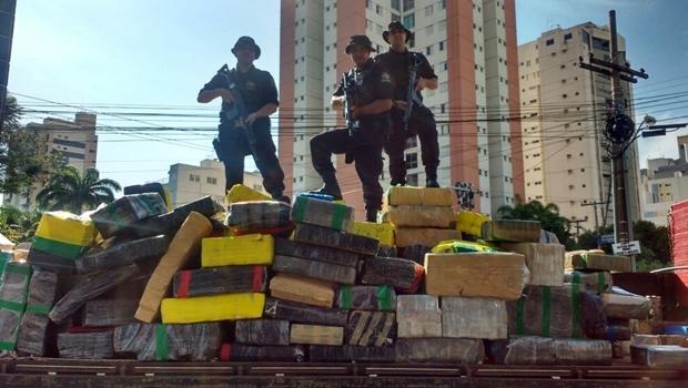 Policiais mostram o carregamento da droga encontrada no galpão no setor | Foto: Divulgação PM5
