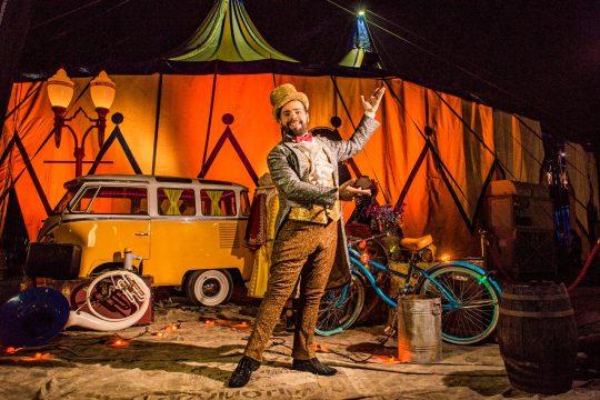 #Paracegover sócio do circo Reder aparece com cartola marrom, calça da mesma cor e terno. Atrás apetrechos de circo como bicicleta, kombi bem pequena, lona circense e trumpete enorme.