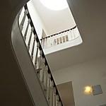 Vista das escadas de acesso aos partamentos iluminadas pelo claraboia