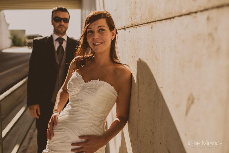 Novia apoyada en el hormigón mientras el novio se acerca en Martos en una fotografía de post boda de Jose Miranda Jaén Martos