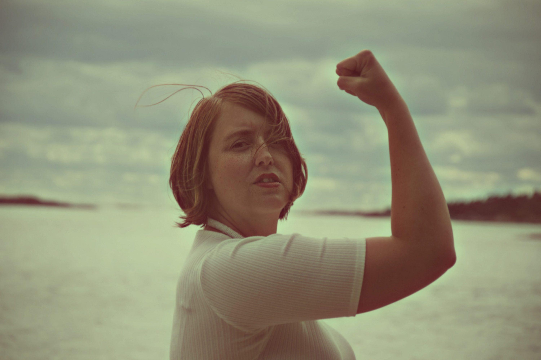 Vi transformerar/We transform - Josephine Bladh AB. Josephine Bladh står upp med havet i bakgrunden och med en knuten näve framför sitt huvud.