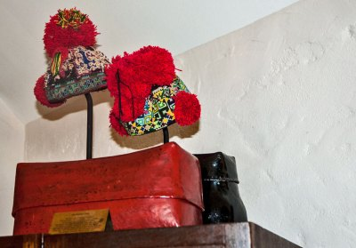 A display of lacquered boxes and intricately embroidered tribal children hats complements the decor of my room.