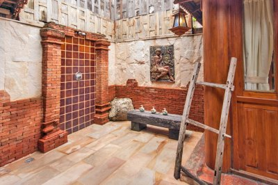 A wall of terracotta tiles framed with rustic brickwork forms the backsplash of my open-air shower.