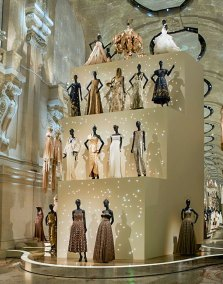 "The final gallery,  the ""Dior ballroom"", is dominated by a towering four-tiered glass case display of ball gowns."