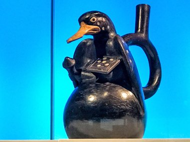 Moche bottle with mother of pearl inlays, reprenting a duck warrior.