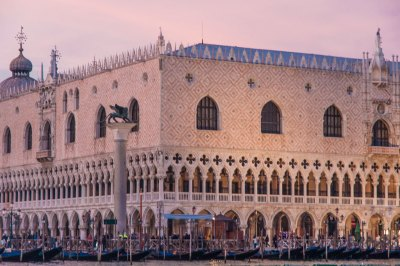 The Doge's Palace and the bronze statue of the Winged Lion of St. Mark at dusk.