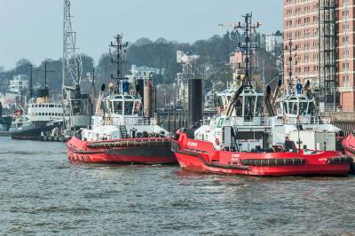Powerful tug boats stand at the ready it to guide ships into the port.