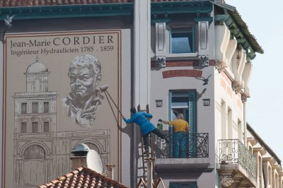 The Jean Marie Cordier mural memorializes the local engineer who developed the steam device to pump water from the River Orb to the fountains of the old town in 1827.