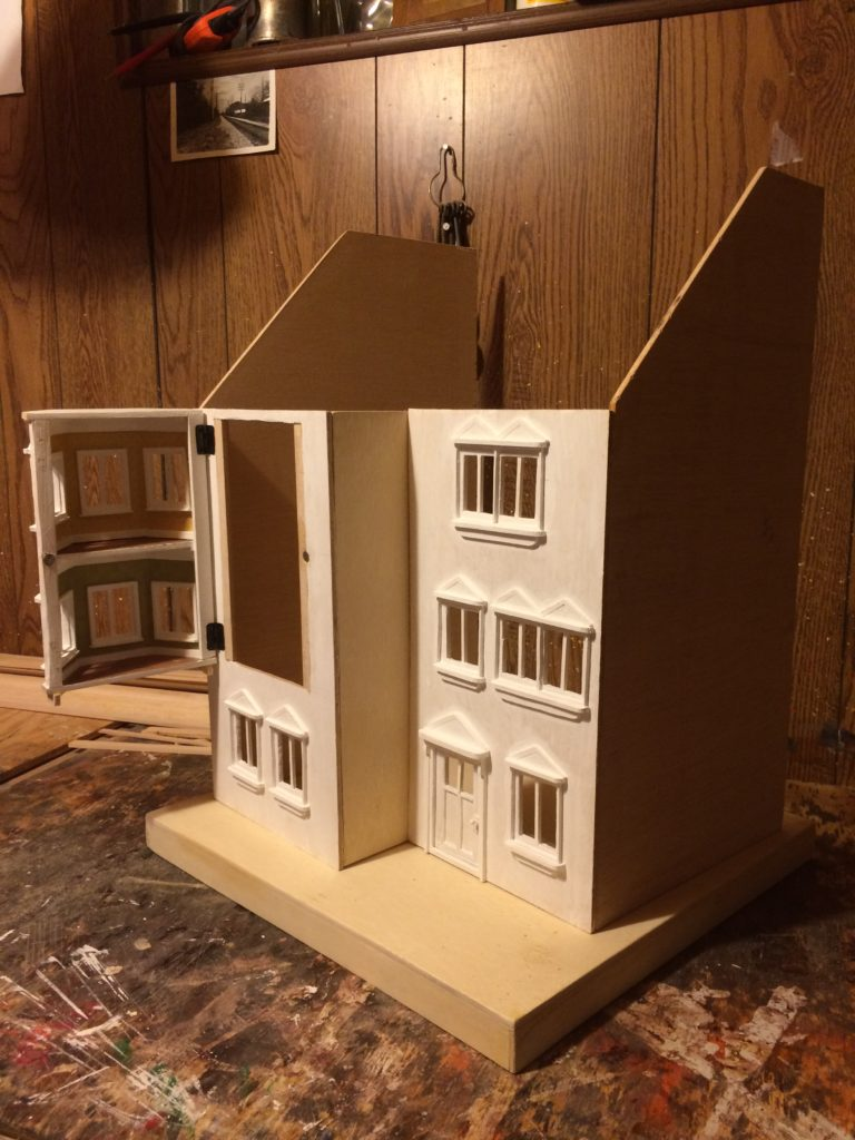 Dollhouse half-assembled and primed in white paint