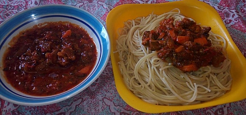 Serving boiled spaghetti with bolognese sauce