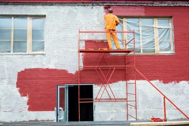 homme peignant une façade en rouge