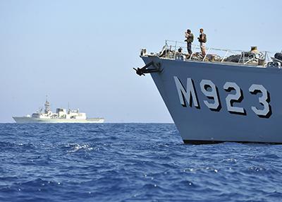 Le NCSMCharlottetown assure la sécurité pendant l'opérationUnified Protector alors que le chasseur de mines belge M923 Narcis, exécute des opérations de lutte contre les mines dans le port de Misourata, près de la côte de la Libye, en mai2011.