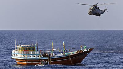 Sous la protection d'un hélicoptèreSeaKing, l'équipe d'arraisonnement du NCSMCharlottetown effectue une fouille à bord d'un boutre dans le golfe d'Aden, dans le cadre de l'opérationArtemis, en mai2012.