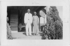 Elder African American couple standing on a porch.