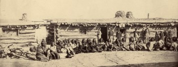 Military camp with Native Americans sitting on ground