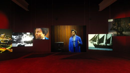 Multi-screen images of actor portraying Frederick Douglass in a dark exhibition space.