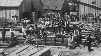 Group of Black men sitting on lumber and standing in pose for a group photograph.