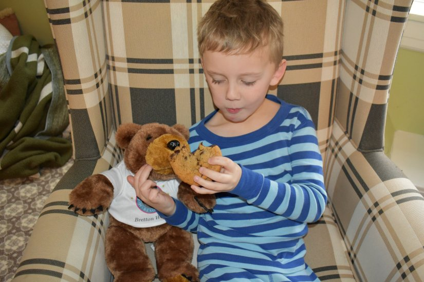 Andrew feeding a cookie to his bear