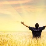 Man in field with hands lifted to God