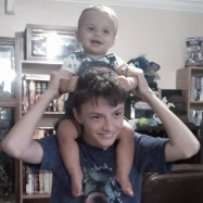 baby brother on big brother's shoulders