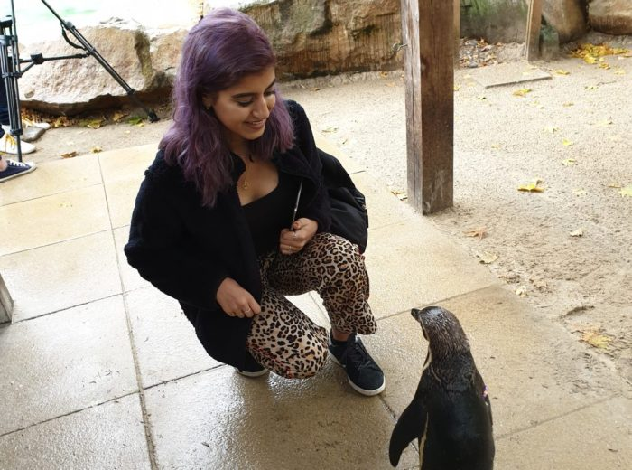 Chandni Sembhi kneeling down next to a penguin